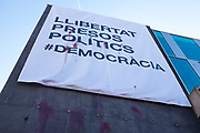 "Defaced poster on the town hall, or ajuntament of Sant Cugat del Valles, Barcelona. The poster, which replaces an earlier one torn down by far-right protestors, reads ""Liibertat Presos Politics"" - Freedom for Political Prisoners in support of Catalan government ministers and civil society leaders jailed by Spanish government.  This version has been bombarded with paint bombs."