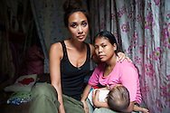 UK celebrity Myleene Klass weeps as she hugs Vilma Tacuyo, 20, while Vilma breastfeeds her youngest child, Ulderico (10 months), in their one room home in an urban slum in Paranaque City, Metro Manila, The Philippines on 18 January 2013. Vilma had raised her first 3 children on formula and had to cut down on food for her family to afford it. Both John Ashley, 4, and Justin, 3, are malnourished and stunted, and after losing one of her children, she now breastfeeds her youngest, Ulderico. Photo by Suzanne Lee for Save the Children UK