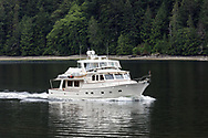 """A small yacht the """"Balladeer"""" leaves Burgoyne Bay and heads into Samsum Narrows.  Photographed from Daffodil Point in Burgoyne Bay Provincial Park on Salt Spring Island, British Columbia, Canada"""