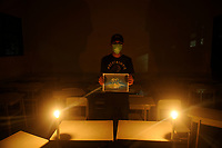 Medan, Indonesia, March 28, 2020: One of three Indonesian people, Rimba Nasution seen using masks and hold posters under the candle lighting in the small campaign action to welcoming Earth Hour moment to resting the earth from the electrical energy used and avoid the harmfull effects of climate changes that trigger the emergence of Corona Virus Disease 19, Photo taken in journalism campus of STIKP in Medan, North Sumatra province, Indonesia on March 28, 2020.