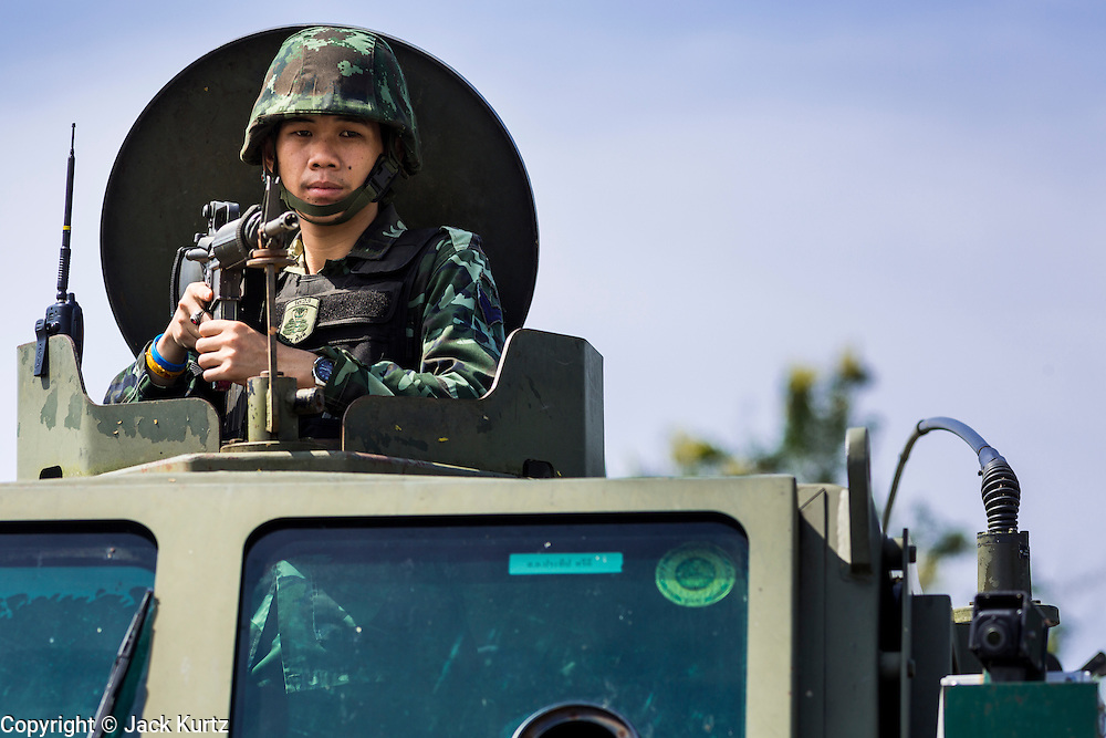 11 JULY 2013 - RAMAN, YALA, THAILAND:  A Thai soldier in a REVA armored car provides security at the scene of an IED attack against members of his unit Thursday. Eight soldiers were injured when the IED exploded under a Thai Army truck carrying soldiers back to their camp after they finished a teacher protection mision. The army routinely dispatches soldiers to protect teachers and Buddhist monks, who have been targeted by Muslim insurgents as representatives of the Bangkok government. More than 5,000 people have been killed and over 9,000 hurt in more than 11,000 incidents in Thailand's three southernmost provinces and four districts of Songkhla since the insurgent violence erupted in January 2004, according to Deep South Watch, an independent research organization that monitors violence in Thailand's deep south region that borders Malaysia.   PHOTO BY JACK KURTZ