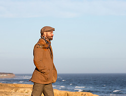 man in the Wintertime standing on a cliff in Montauk, NY
