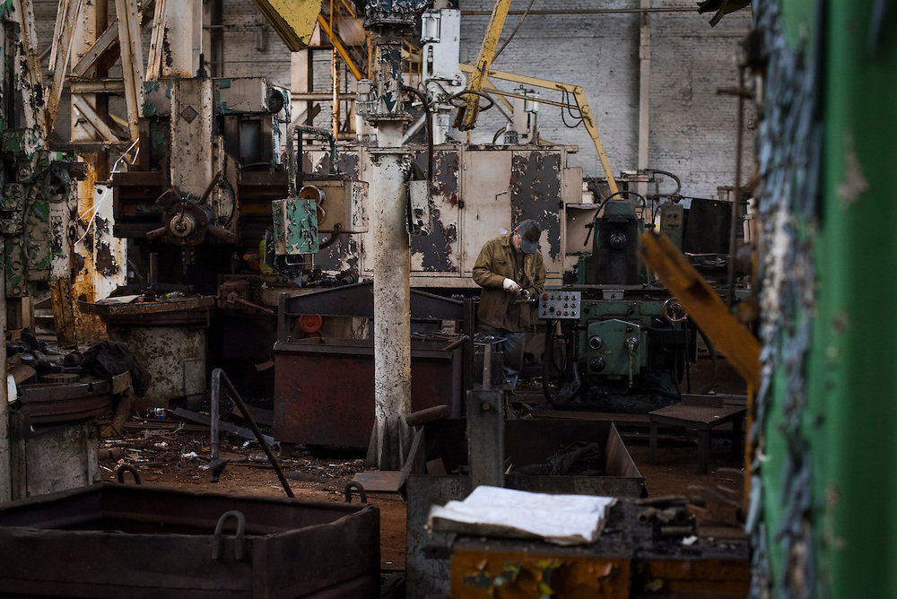 A member of Azov Engineering Group hunts for spare parts and tools among abandoned machinery on September 9, 2015 in Kyiv, Ukraine.