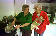 """Monday was the first day of moving back into the Bristol Township Senior Center, nearly three months after the June flooding brought mud and 4 feet of water into the building. In Photo: Jeanne Beyer, of Levittown, PA., nutrition manager, and Helen Nem, of Croydon, PA., a volunteer, clean up the kitchen after they have finished preparing food for the restart of the """"Meals-on-Wheels"""" program."""