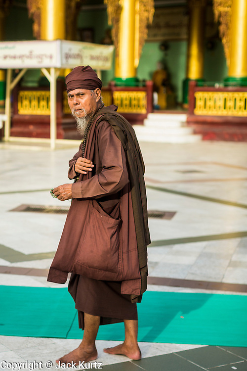 07 JUNE 2014 - YANGON, YANGON REGION, MYANMAR: A Burmese hermit monk walks around Shwedagon Pagoda in Yangon. Shwedagon Pagoda is officially called Shwedagon Zedi Daw and is also known as the Great Dagon Pagoda and the Golden Pagoda. It's a 99 metres (325ft) gilded pagoda and stupa located in Yangon. It is the most sacred Buddhist pagoda in Myanmar with relics of the past four Buddhas enshrined within: the staff of Kakusandha, the water filter of Koṇāgamana, a piece of the robe of Kassapa and eight strands of hair from Gautama, the historical Buddha.   PHOTO BY JACK KURTZ