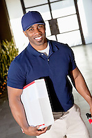Tilt image of a happy African American delivery man looking at camera
