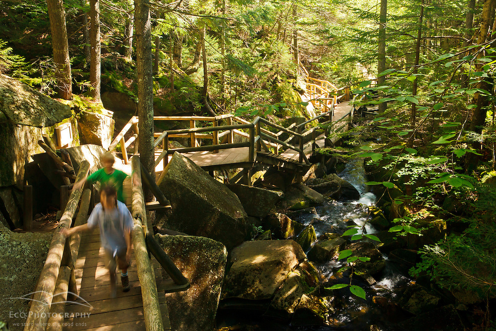A young brother and sister walk on a bridge at Lost River Gorge in New Hampshire's White Mountains. North Woodstock.