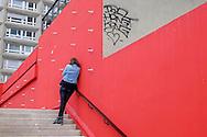 La Dalle Tolbiac, 13 ème arrondissement, Paris. Une femme contre un mur rouge. / The Dalle Tolbiac 13th arrondissement, Paris. A woman against a red wall.