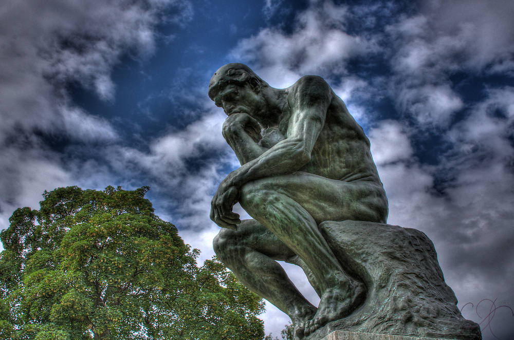 Rodin's masterpiece: The Thinker - Le Penseur- contemplating deeply underneath a summer sky