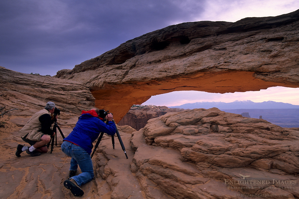 Photographer taking pictures of Mesa Arch, Island in the Sky District, Canyonlands National Park, UTAH