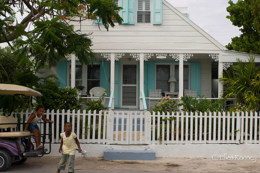 Children getting out of a golf cart in front of a traditional clapboard house;<br /> Dunmore Town, Harbour Island, The Bahamas