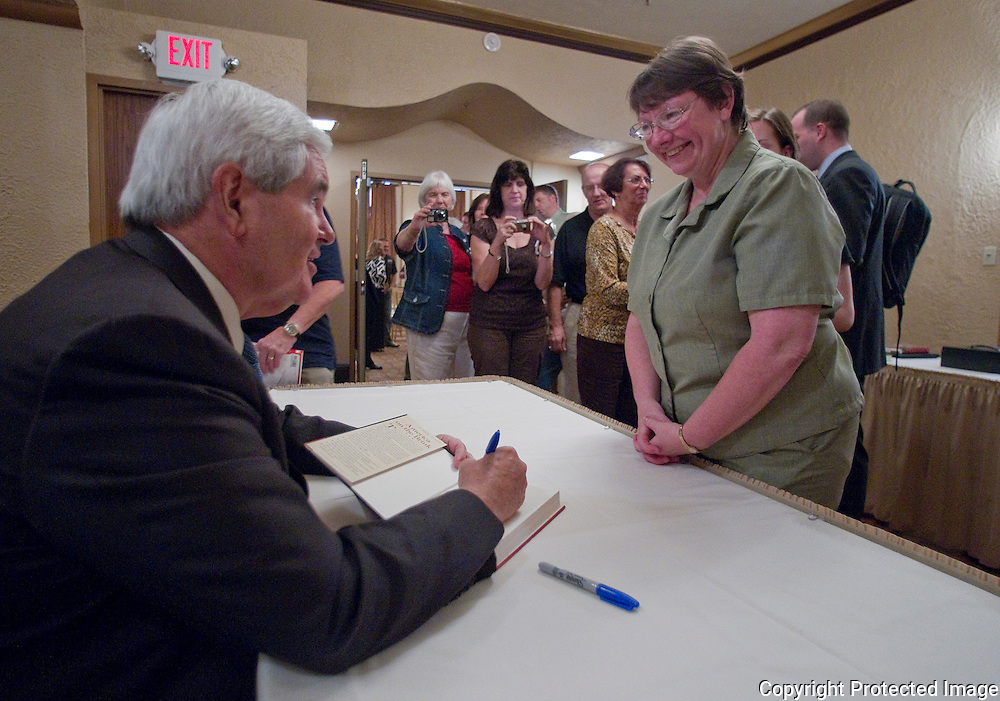 Former House Speaker Newt Gingrich (from left) autographs a book for Cathy Meier after speaking to a gathering of Iowans for Tax Relief at the Sky Event Centre in Waterloo, Iowa on Thursday September 9, 2010. (Stephen Mally for The New York Times)