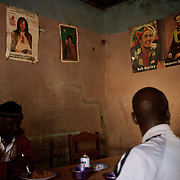 January 19, 2013 - Niono, Mali: Locals take lunch at a restaurant, with Kaddafi, Bob Marley and Emperor Haile Selassiei poster displayed on the wall, in Niono village, the last government controlled location before Diabaly, a city under islamist militants control since the 14th of January. In the back<br />