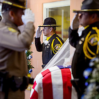 McKinley County Sheriffs officers and Navajo Nation Police officers salute as they change the guard by the casket of McKinley County Sheriffs officer Christopher Tsosie during a memorial service Wednesday at Rehoboth High School in Gallup.