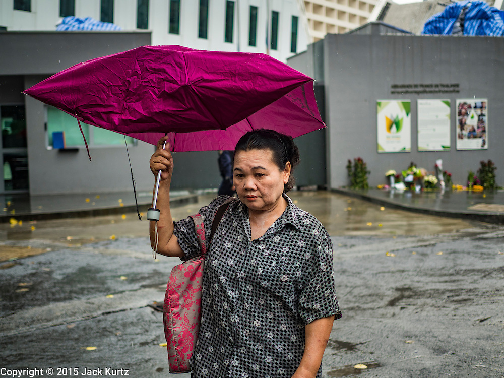 15 NOVEMBER 2015 - BANGKOK, THAILAND:  A woman walks past the gate of the French Embassy in Bangkok, Thailand. Security was heightened at the embassy after terrorists attacked civilian targets in Paris, France, on Nov. 13. The terrorists, affiliated with IS/ISIL killed more than 120 people. People left flowers at the gate to the embassy.         PHOTO BY JACK KURTZ