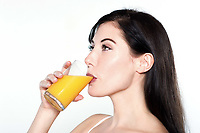one beautiful young caucasian woman drinking orange juice on studio isolated white isolated background