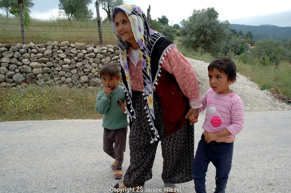 Blind grandmother being led by grandchildren along road through small hill village in Southern Turkey.