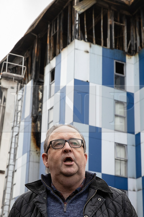 "© Licensed to London News Pictures. 16/11/2019. Bolton, UK. DAVID GREENHALGH of Bolton Council at a press conference at the site of the blaze . Firefighters work at the scene where a fire broke out overnight (15th/16th November 2019) at a block of flats known as "" The Cube "" , in Bolton Town Centre . At least two people are known to have been treated by paramedics at the scene of the six-story block , which is occupied by students of the University of Bolton . Photo credit: Joel Goodman/LNP"