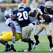 Navy Running Back Gee Gee Greene #21(Right) runs around team mate Darius Staten (middle) who blocks Delaware Cornerback Tim Breaker #3 (left) on a rushing play Saturday Sept. 3, 2011 at Marine Corps Memorial Stadium in Annapolis Maryland.<br /> <br /> Navy would go on to defeat Delaware 40-17 Navy leads the all-time series against the Blue Hens, 9-7, including a 35-18 victory in 2009 when quarterback Ricky Dobbs rushed for five touchdowns.  <br /> <br /> Navy will hit road for a show down with Western Kentucky next Saturday Sept. 10, 2011 in Bowling Green, Ky.