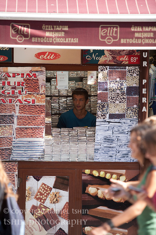 Pedestrians walking past a sweets stall on ?stiklal Avenue, a walking street, in Beyo?lu on a summer afternoon.