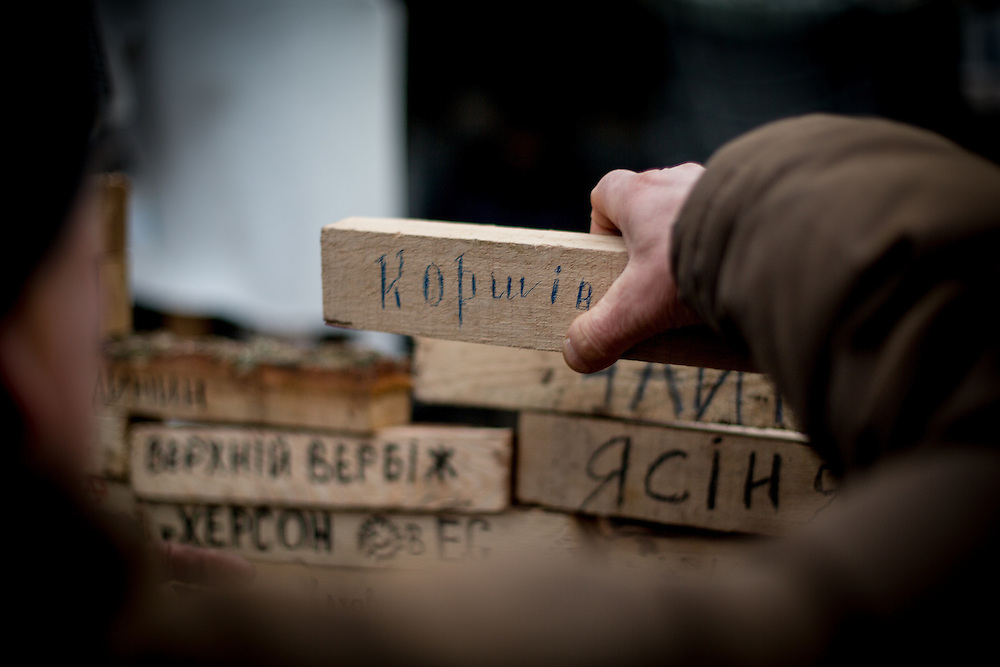 A man puts a piece of wood, with the name of his village written on it, onto a wall made with other pieces of wood with the names of other Ukrainian towns.