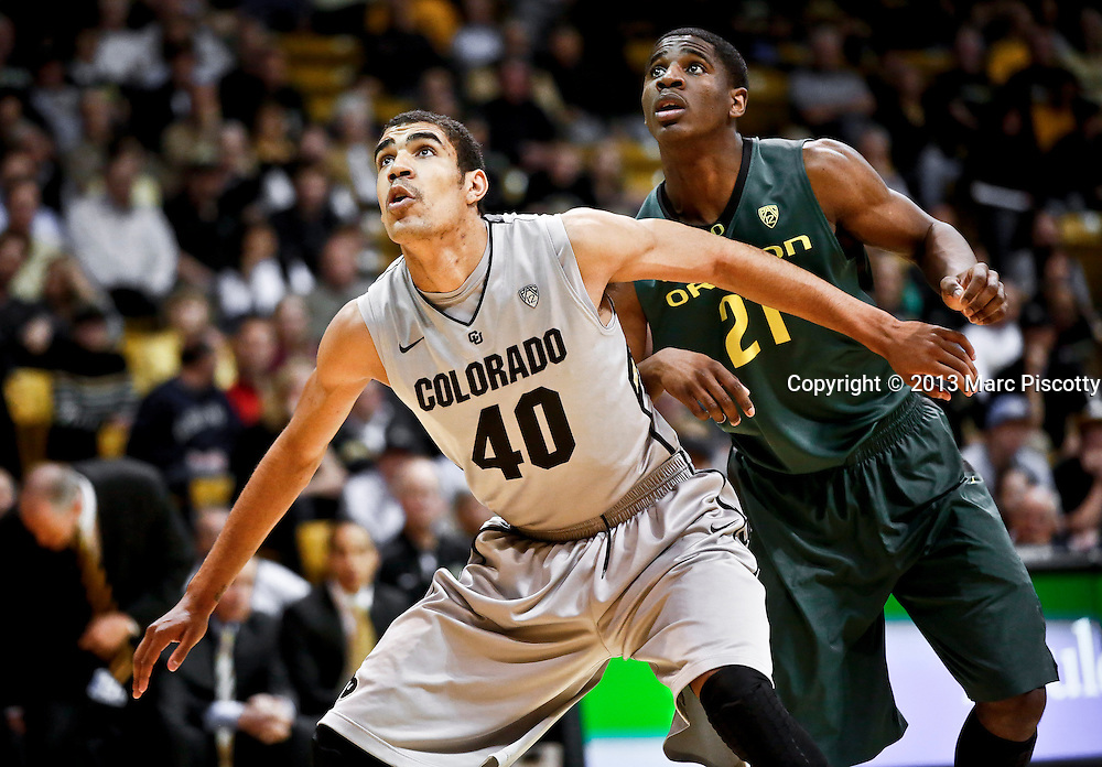 SHOT 3/7/13 7:07:42 PM - Colorado's Josh Scott #40 boxes out Oregon's Damyean Dotson #21 under the basket during their Pac-12 Conference regular season basketball game at the Coors Events Center on the University of Colorado campus in Boulder, Co. Colorado won the game 76-53..(Photo by Marc Piscotty / © 2013)