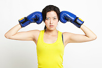 Portrait of young Asian woman in yellow tank top wearing boxing gloves against white background