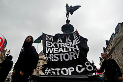 """© London News Pictures. 11/06/2013. London, UK.  A banner reading 'MAKE EXTREME WEALTH HISTORY, #STOP G8"""" hung on the memorial fountain in Piccadilly Circus, central London during an An Anti-G8  demonstration today (Tues). The G8 Summit is due to take place in Norther Ireland early next week.  Photo credit: Ben Cawthra/LNP"""