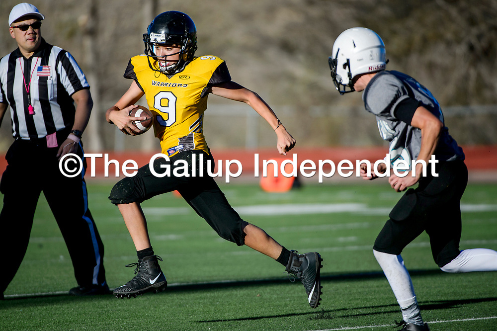 Kennedy Middle School Warrior Blas Saucedo (9) sprints past the Gallup Middle School Mustang defense Wednesday at Angelo DiPaolo Stadium in Gallup.