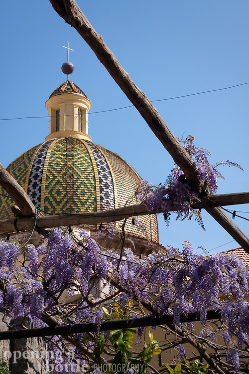 The dome of Santa Maria Assunta, the main church in Positano, rises over a trellised walkway covered in lavender flowers. Positano, Amalafi Coast, Campagna, Italy.
