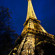 Paris, France - March 25, 2010:  View looking up at the Eiffel Tower illuminated at dusk.   The Eiffel Tower, the most visited paid monument in the world, is lite by more than 20,000 light bulbs.