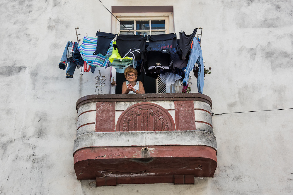 A woman smiles from the laundry-covered balcony of her home in Havana