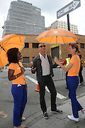 Noted fashion photographer and TV star Nigel Barker is protected from any chance of rain by the AccuWeather MinuteCast street team at New York Fashion Week, on Saturday, Sept. 12, 2015. The AccuWeather MinuteCast Street Team is at it again helping Fashion Week attendees stay stylish and one-step ahead of any possible precipitation. (Photo by Diane Bondareff/Invision for AccuWeather/AP Images)