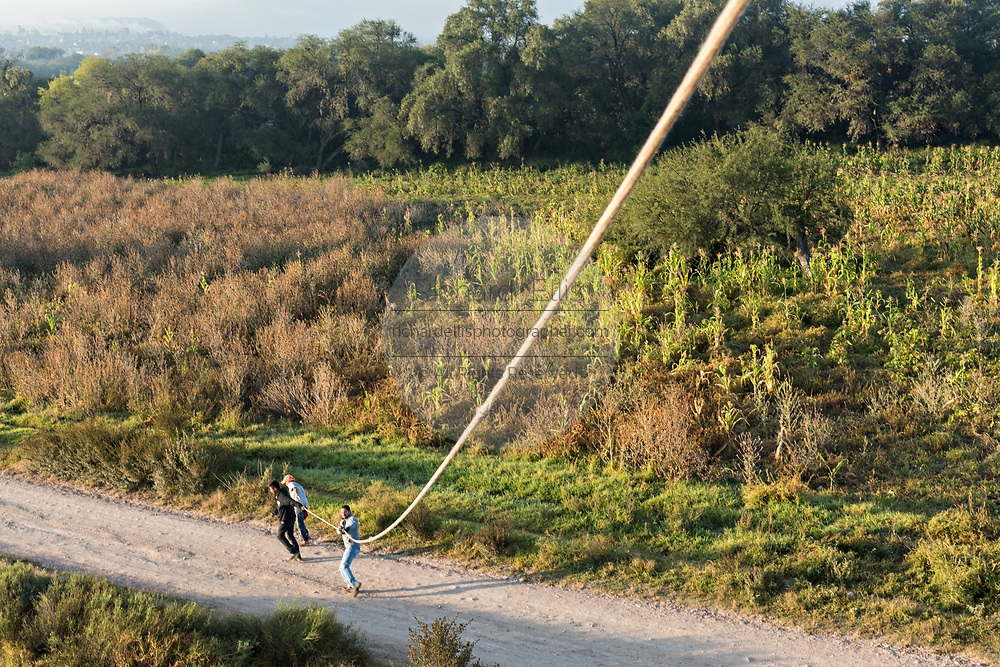 Ground crew guild a descending hot air balloons with a tethered rope to land outside the colonial city of San Miguel de Allende, Mexico.