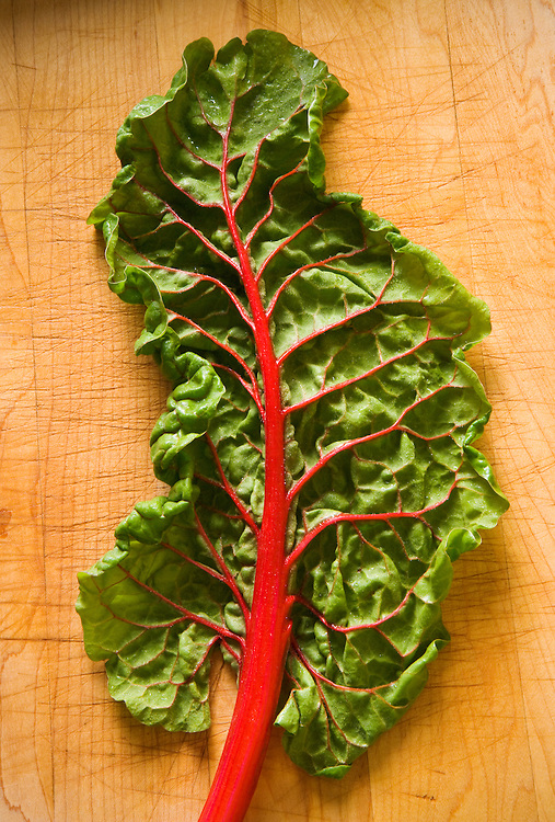 Studio still lifes of swiss chard on a cutting board.