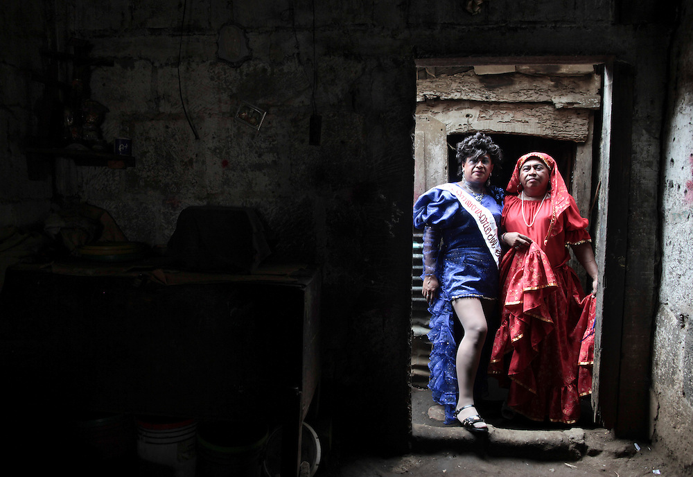 """Two travestites men posses for a picture inside a house during a celebration called """"Torovenado"""" in honor of the patron saint San Jeronimo in Masaya near of Managua, Nicaragua, Sunday, Oct. 30, 2011. (AP Photo/Esteban Felix)"""