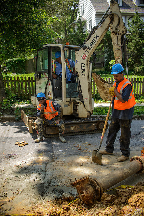 Photo by Matt Roth<br /> <br /> Baltimore City Department of Public Works employees Nathanial Copeland, left, backhoe operator Stanley Maith, middle, and laborer Charles Lee, right, take a short break while replacing a fire hydrant at the intersection of Tyndale Ave., and Canfield Ave. in Baltimore, Maryland on Wednesday, May 29, 2013.