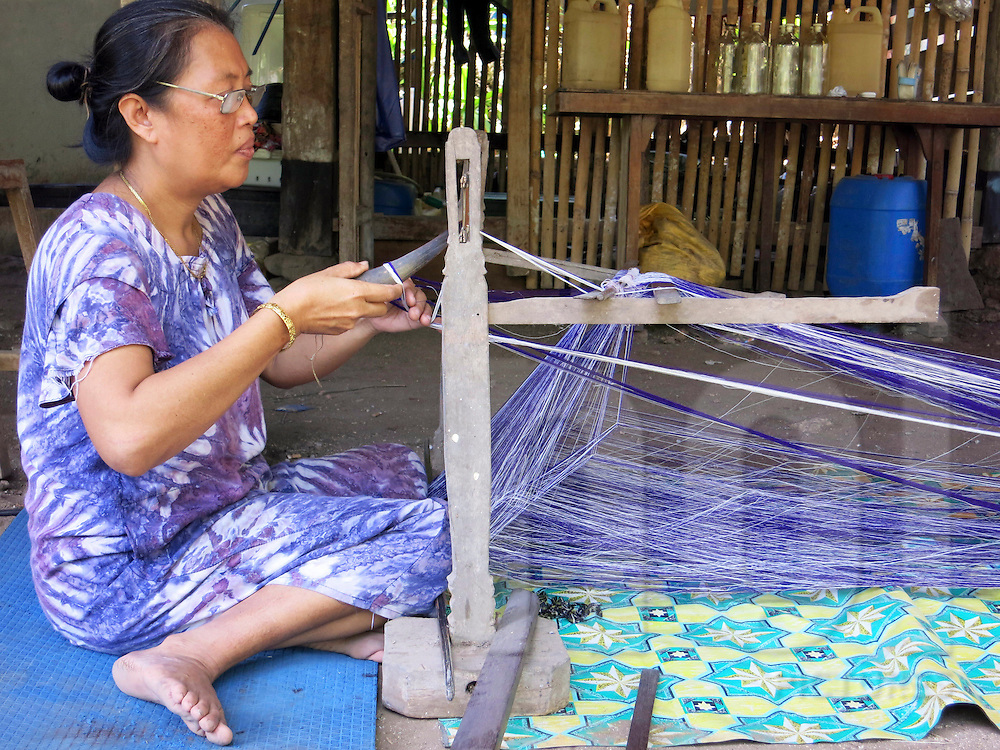 A local woman weaves with purple and white thread in Bira, South Sulawesi, Indonesia, Southeast Asia