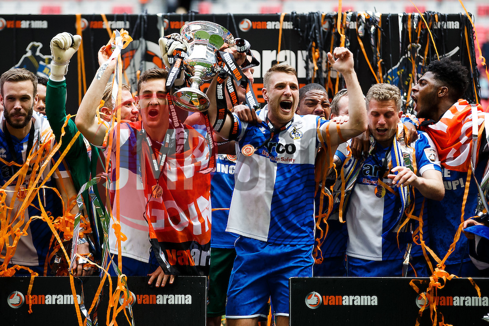 Lee Brown of Bristol Rovers lifts the trophy at the winners board after they win the match on penalties  to secure promotion to the Football League 2 - Photo mandatory by-line: Rogan Thomson/JMP - 07966 386802 - 17/05/2015 - SPORT - FOOTBALL - London, England - Wembley Stadium - Bristol Rovers v Frimsby Town - Vanarama Conference Premier Play-off Final.