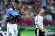 FUSSBALL  EUROPAMEISTERSCHAFT 2012   HALBFINALE Deutschland - Italien              28.06.2012 Mario Balotelli (li, Italien) jubelt nach seinem Tor zum 0:1. Philipp Lahm (re, Deutschland) wendet sich enttaeuscht ab