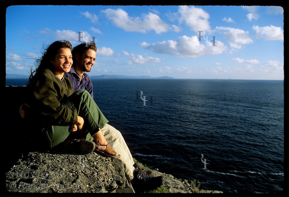 Honeymooners Celestiel East-Balson & Oliver Balson sit atop rock wall at Slea Head on a summer evening; Dingle Peninsula, Ireland.