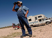 Minuteman Project volunteer Fred Puckett of Arizona watches for illegal aliens at the US/Mexico border fence near Naco, Arizona on Monday, April 4, 2005. The Minuteman Project is an all-volunteer group monitoring the US/Mexico border in Arizona for the month of April, reporting all illegal border crossers to the US Border Patrol.<br />