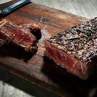 Blue New York strip steak on cutting board .
