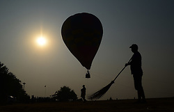 October 17, 2016 - Allahabad, India - An indian munnicipal worker sweeps near a  hot air balloon ,on the banks of holy Sangam,the confluence of Ganges River,Yamuna river and Mythological Saraswati river, in Allahabad on October 17,2016. The State Government and Administrative officials conduct an awareness initiative  for Electors parternership programme ahead of state assembly elections in Uttar Pradesh. (Credit Image: © Ritesh Shukla/NurPhoto via ZUMA Press)