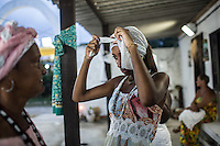 RIO DE JANEIRO, BRAZIL - JANUARY 24: Andressa Bispo, 20, ties a head scarf before a candomble ceremony, in Rio de Janeiro, Brazil, on Saturday, Jan. 23, 2015. Brazil's Afro-Brazilian religions which in recent years have come under increasing threats and prejudice, particularly from the growing number of evangelical churches. Candombl&eacute; originated in Salvador, Bahia at the beginning of the 19th century when enslaved Africans brought their beliefs with them. Umbanda and candombl&eacute; are Afro-Brazilian religions practiced in mostly Brazil. <br /> (Lianne Milton for the Washington Post)