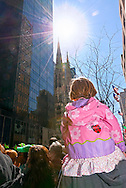 MARCH 17, 2011 - MANHATTAN:  MANHATTAN: Sunflare, little girl on father's shoulders watching 5th Ave parade, child seen from below back, St. Patrick's Day Parade sunflare over St. Patrick's Cathedral in background. Little girl wearing spring jacket with pink and lilac design with ladybug, and dress ruffle showing. EDITORIAL USE ONLY