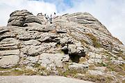 People scrambling on a granite tor near Haytor, Dartmoor national park, Devon, England, UK