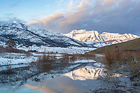 Sunrise at Deer Creek Reservoir with Mount Timpanogos illuminated by the early sunrise and reflecting in the calm waters of an early Winter morning.