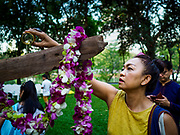 "17 MARCH 2018 - BANGKOK, THAILAND:  A woman pours floral water into an altar in Lumpini Park during a ""sticky rice merit making"" in the park in Bangkok. Sticky rice merit making is a merit making in the Isan / Lao style, when people present small amounts of cooked sticky rice (also known as glutinous rice) to Buddhist monks. Isan is the northeast region of Thailand.    PHOTO BY JACK KURTZ"