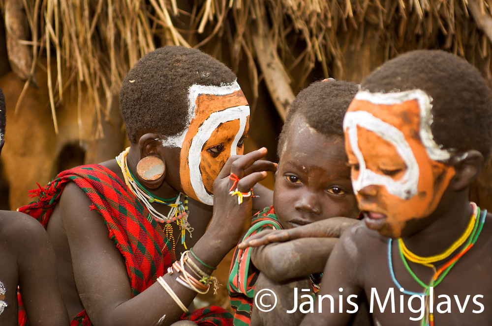 Young Suri (Surma) tribe boy inspecting another boy's ear near Kibish village, Omo region, Ehtiopia, Africa.
